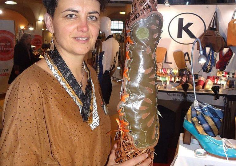 claire choffel creatrice de mode se presnet de trois quart et monte une grande guetre en cuir kaki et camel